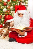 Image of little girl reading book with Santa Clause, small child with grandpa wearing red festive co