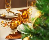 Photo of luxury Christmastime table setting, holiday dinner in restaurant, festive white dinnerware