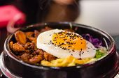 pic of kimchi  - closeup bibimbap with fried egg in a heated stone bowl korean style food - JPG