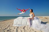 image of sweethearts  - Happy groom flying on bed to his sweetheart on the beach  - JPG