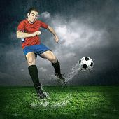 Football player with ball in action under outdoors rain