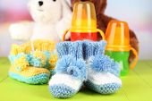 Composition with crocheted booties for baby, bottle, toy and other things on color background