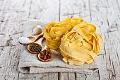 raw egg pasta and spices  on rustic wooden background