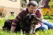 image of working animal  - mentally disabled woman is lying with dog on a lawn - JPG