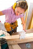 stock photo of hand drill  - Female carpenter at work using hand drilling machine - JPG