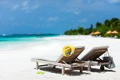 Lounge chairs on a beautiful tropical beach at Maldives