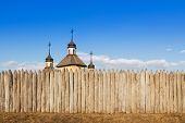 stock photo of log fence  - Wooden church with three steeples and crosses is behind a fence of logs against the sky - JPG