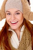 stock photo of vivacious  - Vivacious gorgeous young woman in winter fashion laughing as she holds her gloved hands to her knitted beanie hat - JPG