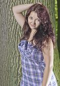 image of wench  - Young girl standing near a tree trunk - JPG