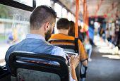 stock photo of tram  - Handsome hipster modern man using digital tablet in tram - JPG
