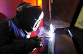 image of tig  - worker Cutting metal with mig welder in construction site - JPG