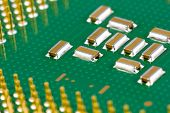 stock photo of capacitor  - Small SMD capacitors on green processor with golden pins - JPG