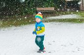 stock photo of pullovers  - Winter portrait of a cute little boy under the snowfall - JPG