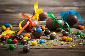 stock photo of easter candy  - Chocolate Easter Eggs Over Old Wooden Background - JPG