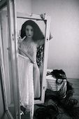 foto of creepy  - creepy young woman with long curly hair in scary room black and white - JPG