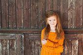 picture of pullovers  - Outdoor portrait of a cute little girl standing next wooden door - JPG