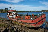 stock photo of derelict  - Derelict fishing boat stranded on the shore in Castro - JPG