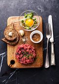 foto of tartar  - Beef tartare with salad and garlic toasts on dark marble background - JPG