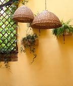 stock photo of lamp shade  - Wicker lamps shade against a background of yellow wall - JPG