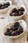foto of ceramic bowl  - Marinated black olives in white ceramic bowl on white wooden background - JPG