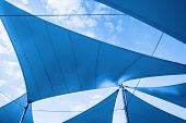 stock photo of toned  - Awnings in sails shape over cloudy sky background - JPG