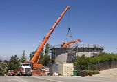 foto of boom-truck  - very large 265 ton crane lifting smaller crane from within a concrete water tank construction project in a hillside community in Northern California - JPG