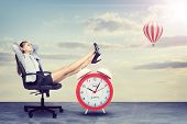 foto of legs air  - Businesswoman sitting in office chair with her hands clasped behind her head and her feet up on alarm - JPG