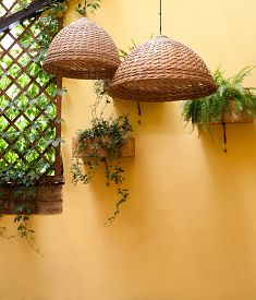 pic of lamp shade  - Wicker lamps shade against a background of yellow wall - JPG