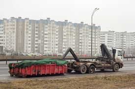 foto of truck-stop  - Truck with waste container and flat tire stopped on the load - JPG