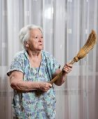 foto of broom  - Old angry woman threatening with a broom at home - JPG