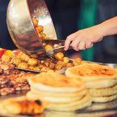 picture of buffet  - Buffet stall with grilled meat, potatoes and pancakes dished out
