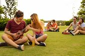 stock photo of ukulele  - Vietnamese young couple sitting on the grass and trying to play ukulele - JPG