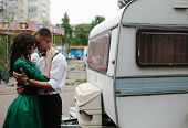 foto of trailer park  - man and woman is hidden from view behind a trailer in the park with attractions - JPG