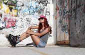 foto of roller-skating  - Sitting Girl With Roller Skates On urban wall Background - JPG
