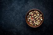stock photo of peppercorns  - Peppercorns in a wooden bowl on a dark background - JPG
