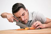 picture of over counter  - Young man cutting carrot over gray background - JPG