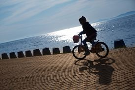 picture of superimpose  - Girl on bike on the seafront promenade at sunset - JPG