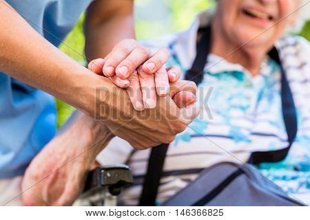 Nurse consoling senior woman holding