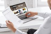 business, blogging, technology and people concept - businessman with internet blog page on laptop co poster