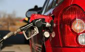 stock photo of bowser  - cropped photo showing a bowser hose filling a car with gasoline or petrol.