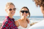 Постер, плакат: Happy smiling best friends embrancing at seaside Two girls friends laughing with their friend Best