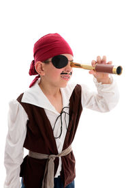 stock photo of pirate ship  - A young boy pirate looking through a monoscope in search of treasure or ships to plunder - JPG