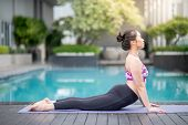 Young Asian Attractive Woman Doing Yoga Exercise With Bhujangasana Posing (cobra Pose) Near Swimming poster