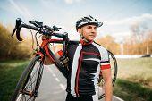Bycyclist keeps the bike on shoulder after biking poster