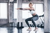 Attractive Young Woman Doing Squat Exercise At The Gym. poster