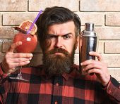 Barman With Beard, Stylish Hair And Strict Face On Light Brick Wall Background. Man Holds Glass, Del poster
