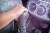 Drivers hand changing gear with gear shift lever. Operating manual gearbox concept poster