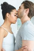 Side View Of Tender Multiethnic Couple In Love At Home poster