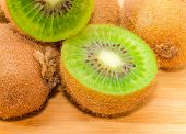 Background Of Whole Ripe Fuzzy Kiwifruits And Fruit Cut In Half Closeup poster