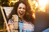 Photo of ecstatic brunette woman 18-20 clenching fist and screaming while sitting in deck chair duri poster